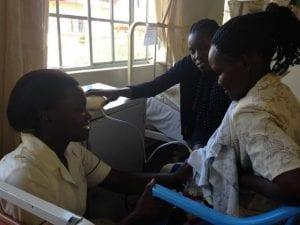 Bertha (nutritionist) and Maureen (nurse on nutrition team) teaching a mum to use a breast pump